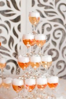 Pirámide de cóctel con copas de champán en la boda