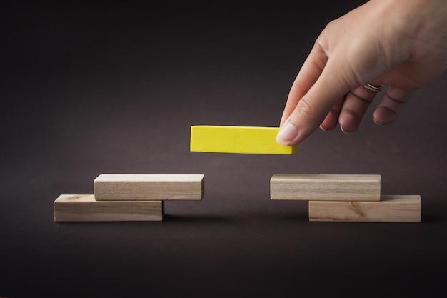 Pirámide de construcción de mano con bloques de madera vacíos, que simboliza la carrera profesional. concepto de líder.