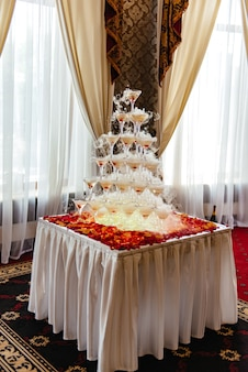 Pirámide de copas de champán con cereza y vapor de hielo seco
