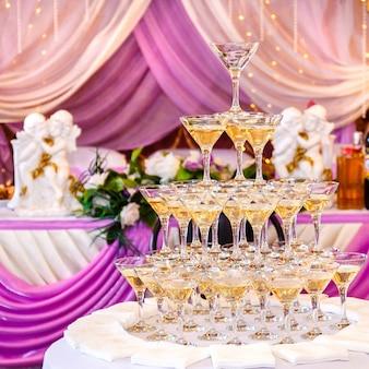 Pirámide de copas con champán en el interior de la boda púrpura.