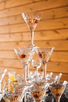 Pirámide de copas de vino con champagne. se vierte champán en los vasos. decoración festiva del evento con una pirámide de copas de champán.