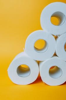 Pirámide de papel higiénico sobre fondo naranja. rollos de papel higiénico blancos durante la pandemia.