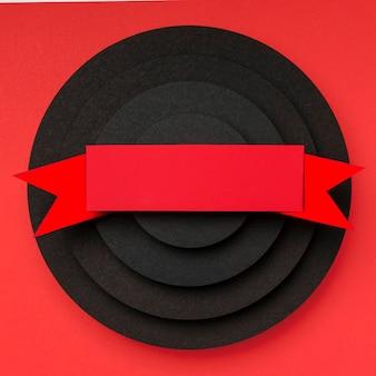 Pirámide de piezas circulares de papel negro y cinta.