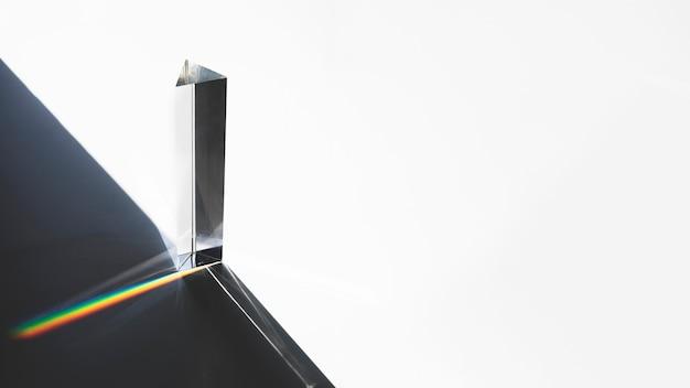 Pirámide triangular de vidrio con efecto de dispersión de luz óptica sobre fondo blanco