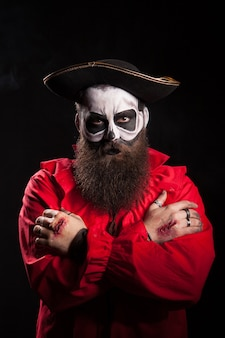 Pirata barbudo aterrador con las manos cruzadas sobre fondo negro. disfraces de halloween