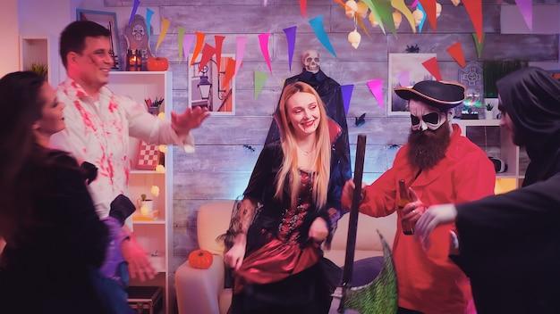 Pirata barbudo con hacha y sus amigos bailando en la celebración de halloween en la habitación decorada