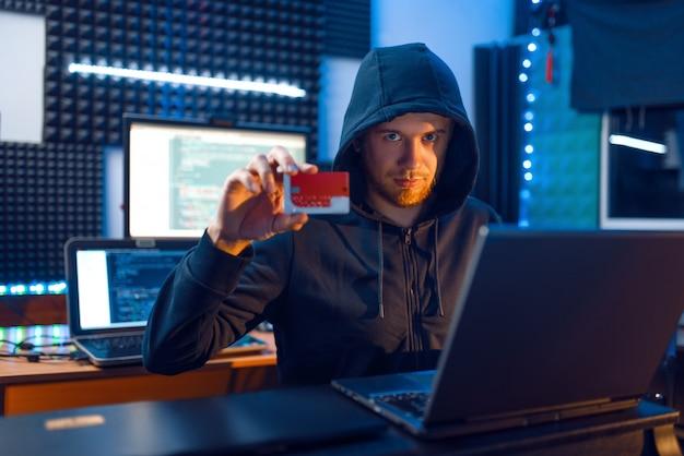 El pirata informático en el capó muestra una tarjeta de crédito bancaria en su lugar de trabajo con una computadora portátil y de escritorio, una contraseña o una piratería financiera, un usuario de darknet.