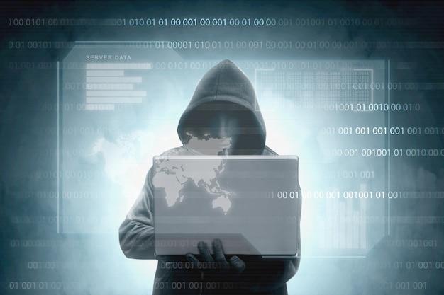 Pirata informático con capucha negra que sostiene una computadora portátil con datos del servidor de pantalla virtual, barra de gráficos, código binario y mapa mundial