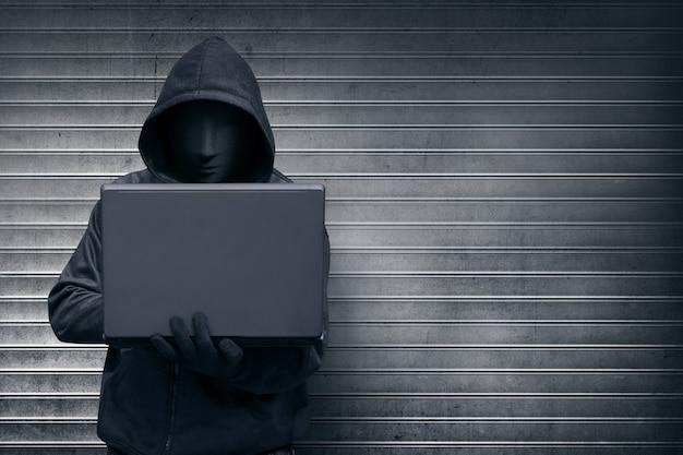 Pirata informático encapuchado con máscara sosteniendo portátil mientras se escribe