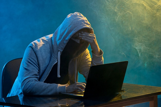 Pirata informático encapuchado que roba información con una computadora portátil