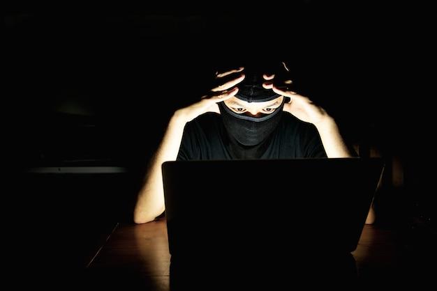 Pirata informático haciendo su trabajo con la computadora portátil en el cuarto oscuro