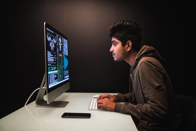 Pirata informático indio que usa computadoras para robar datos en el escritorio oscuro