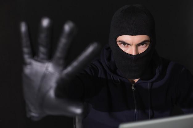 Pirata informático en pasamontañas gesticulando y mirando a la cámara