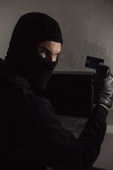 Pirata informático que usa la tarjeta de débito y la computadora portátil