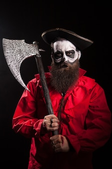 Pirata loco barbudo con su hacha sobre fondo negro. traje de halloween.