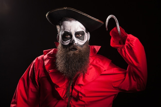Pirata loco y peligroso con un gancho sobre fondo negro. traje de halloween.