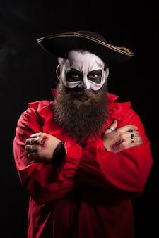 Pirata masculino con un disfraz espeluznante sobre fondo negro para halloween.