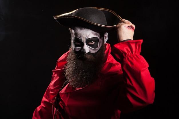 Pirata medieval barbudo y espeluznante con sangre en sus manos sobre fondo negro. disfraz de halloween.