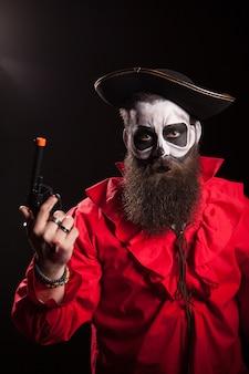 Pirata medieval loco y espeluznante con su pistola sobre fondo negro. traje de halloween.