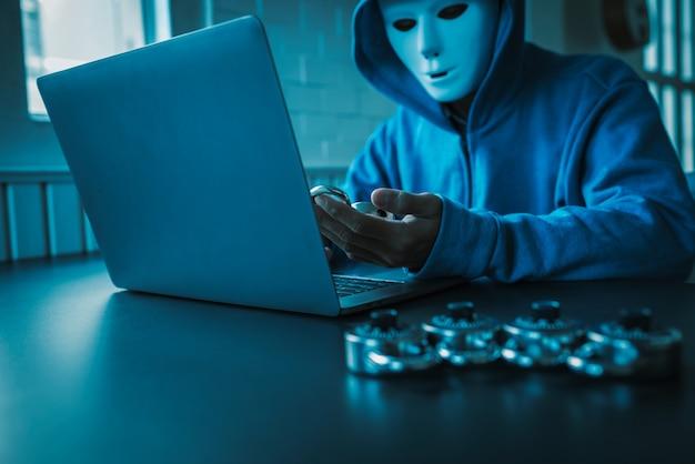 Los piratas informáticos asiáticos usan una máscara usando un ataque cibernético portátil.