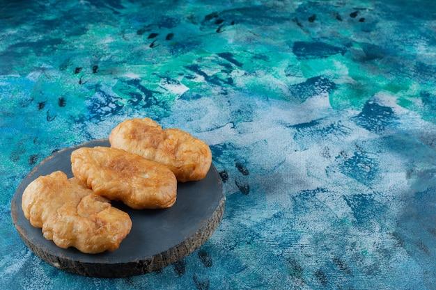 Pirozhki frito a bordo, sobre la mesa de mármol.