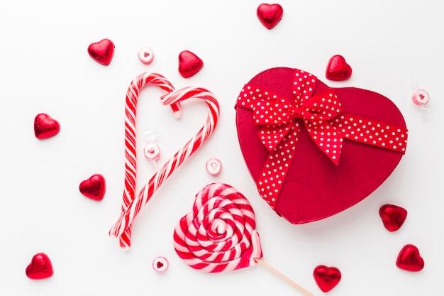 Piruleta de bastón de caramelo y una caja en forma de corazón