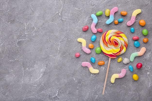 Piruleta de colores y dulces redondos de diferentes colores sobre fondo gris