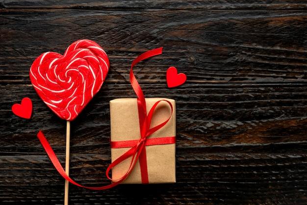 Piruleta en forma de corazón y caja de regalo artesanal para el día de san valentín sobre fondo de madera oscura. concepto festivo, vista superior.