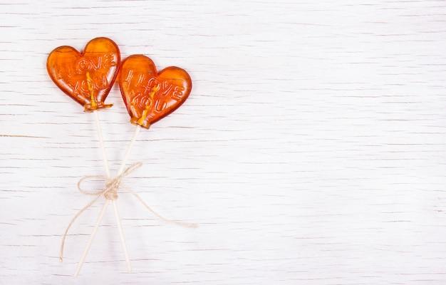 Piruleta en forma de corazón sobre un fondo blanco de madera.