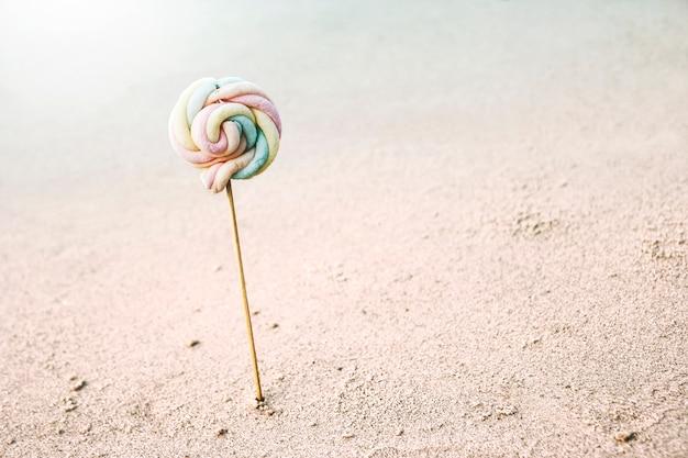 Piruleta de malvavisco en la playa verano mínimo