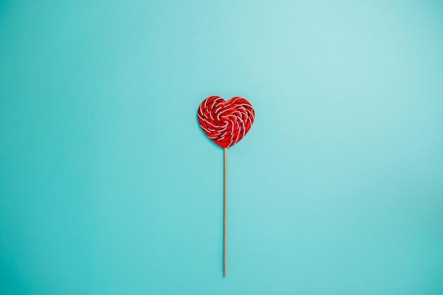 Piruleta roja en forma de corazón con palo largo. una piruleta en el medio.