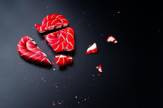 Piruleta rota en forma de corazón sobre un fondo oscuro con espacio de copia