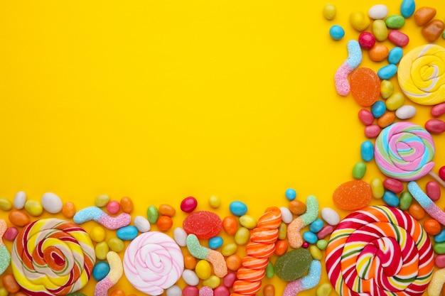 Piruletas de colores y dulces redondos de diferentes colores sobre fondo amarillo