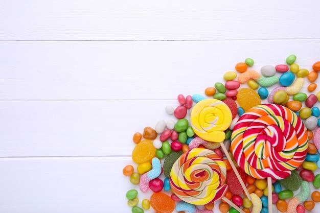 Piruletas de colores y dulces redondos de diferentes colores sobre fondo blanco.