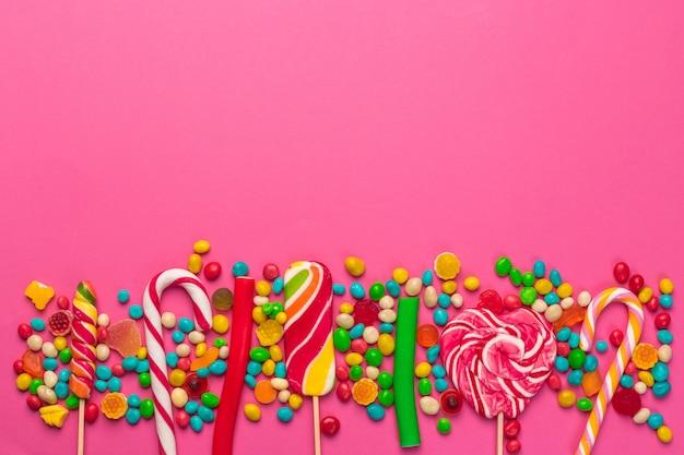 Piruletas de colores sobre un fondo rosa