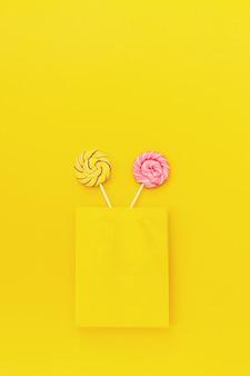 Piruletas dulces redondas dulces con rayas en palo en paquete de papel amarillo. concepto creativo para cumpleaños, fiesta, vacaciones. dulce regalo para una dulce vida. vista superior y endecha plana.