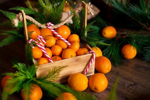 Piruletas de navidad, mandarinas, ramas de un árbol de navidad