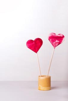 Piruletas rojas en forma de corazón sobre un fondo blanco. postal para el día de san valentín. romántica historia de amor con copyspace.