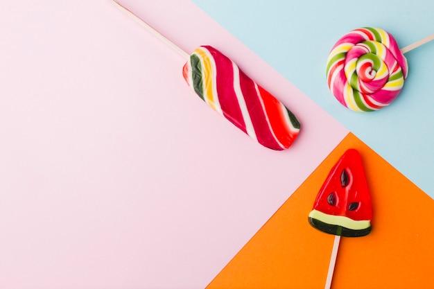 Piruletas de vista superior en mesa colorida