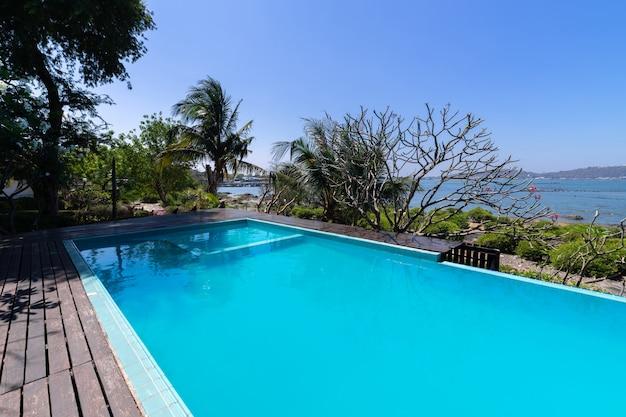 Piscina de agua azul y jardín tropical con fondo de vista al mar.