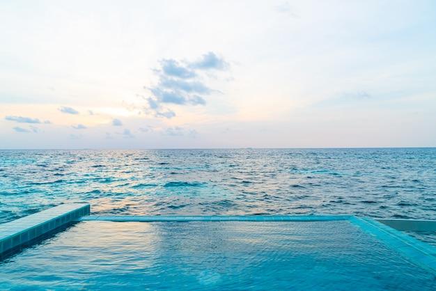 Piscina al aire libre con mar océano y cielo al atardecer