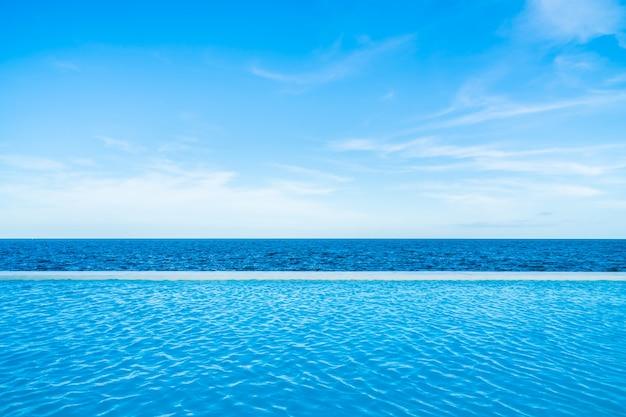 Piscina infinita con vista al mar y al océano en el cielo azul.