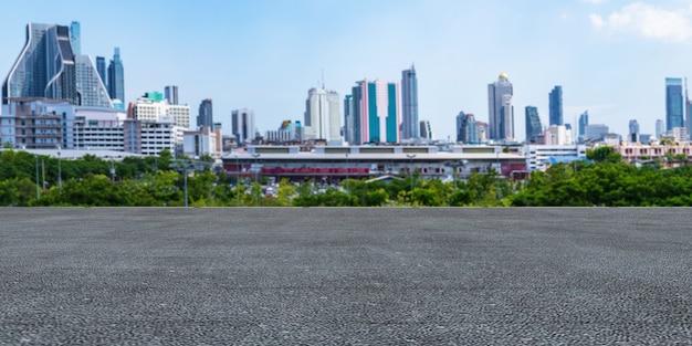 Piso de concreto vacío panorámico e hierba verde en un hermoso parque bajo el cielo azul