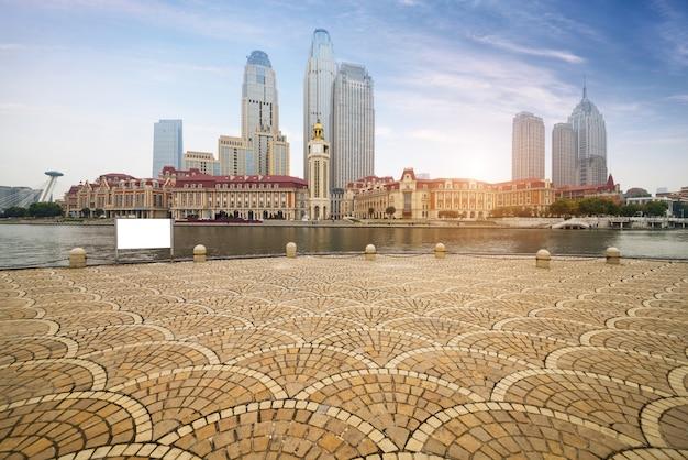 Piso embaldosado vacío y horizonte urbano, china de tianjin.