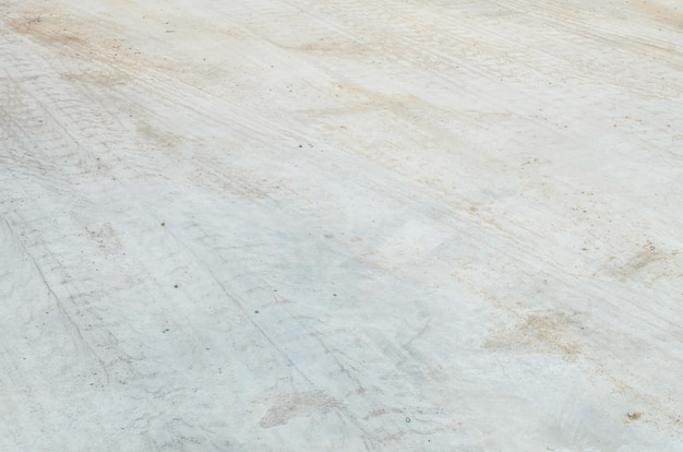Piso de hormigón de superficie de primer plano con fondo de textura de huellas de neumáticos