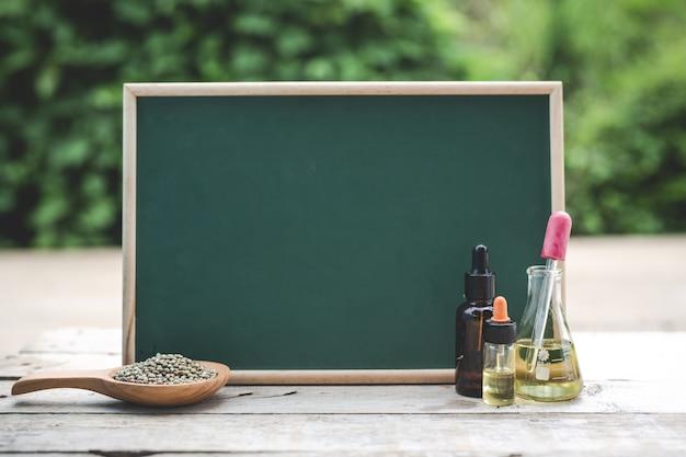 En el piso de madera hay aceite de cáñamo, semillas de cáñamo. y el tablero verde está en blanco para poner texto.