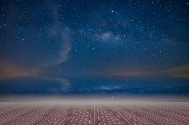 Piso de madera y telón de fondo del cielo de la vía láctea en la noche
