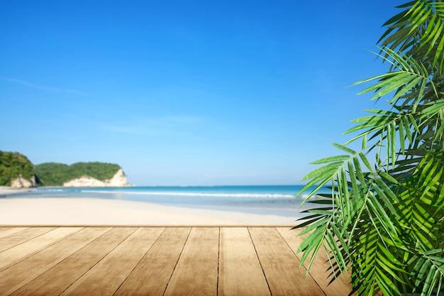 Piso de madera con vista al mar y hoja de palma verde