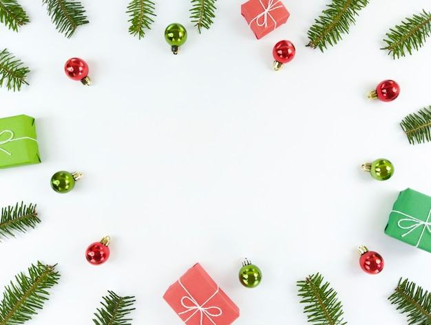 Piso de navidad con espacio de copia en el medio. ramas de árboles, adornos verdes y rojos, cajas de regalo sobre un fondo blanco.