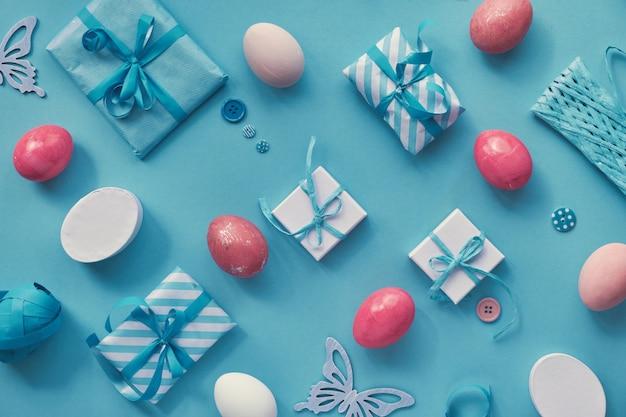 El piso de pascua yacía en blanco y rosa sobre una superficie de papel de menta azul con huevos y regalos